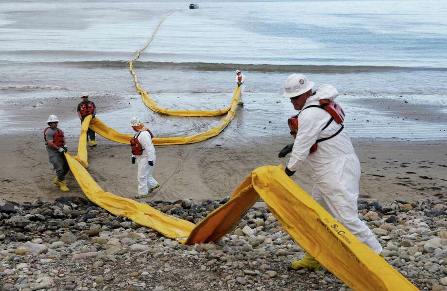 Workers prepare an oil containment boom at Refugio State Beach, north of Goleta, Calif., after a pipeline break created a massive spill in the area this week. More than 7,700 gallons of oil has been raked, skimmed and vacuumed from a spill that stretched across about 9 miles of California coast.  Photo: Jae C. Hong, STF / AP