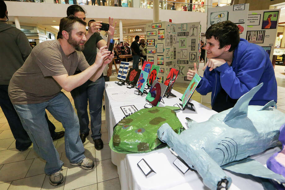 "Ryan and Kristin Hool (from left) take a photo of their son Rowan Hood, 15, and his ""Tron Wolf"" painting made in Ms. Elzner's class at Judson Middle School and on display during the 2015 JISD Art Extravaganza at Rolling Oaks Mall on Wednesday, May 20, 2015.  MARVIN PFEIFFER/ mpfeiffer@express-news.net Photo: Marvin Pfeiffer, Staff / San Antonio Express-News / Express-News 2015"