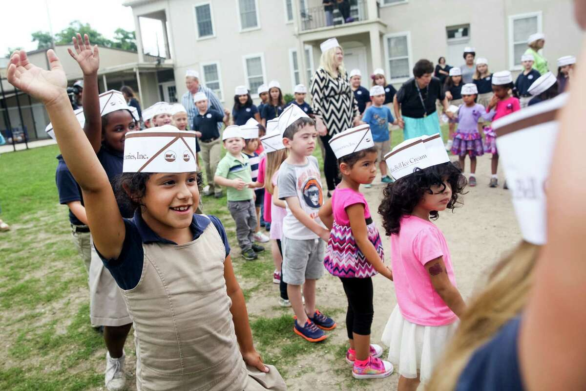First grader Gisele Morales, 7, raises her hand after the students were asked if they missed their Blue Bell ice-cream Friday May 22, 2015 at St. James Catholic School in Seguin, Texas. About 160 students gathered on school grounds along with teachers, parents and the St. James Catholic Church parish priest to pray for those who became sick from eating the ice cream, employees whose jobs were affected, and the return of Blue Bell ice cream to their lunchroom, school events, and their school store.