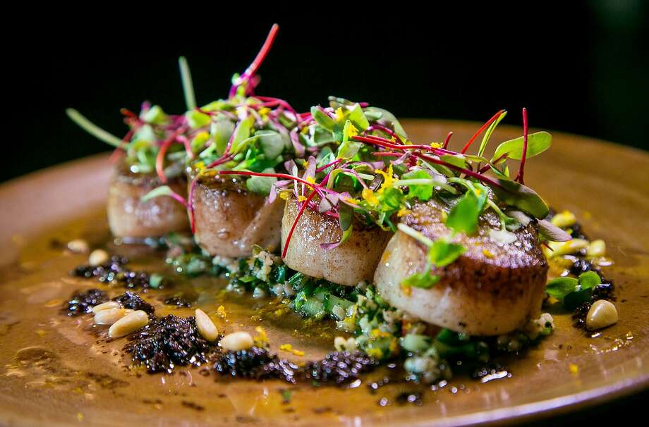 The pan seared scallops come with tabbouleh ringed with black olive puree and orange oil at BDK in the Hotel Monaco in San Francisco. Photo: John Storey, Special To The Chronicle