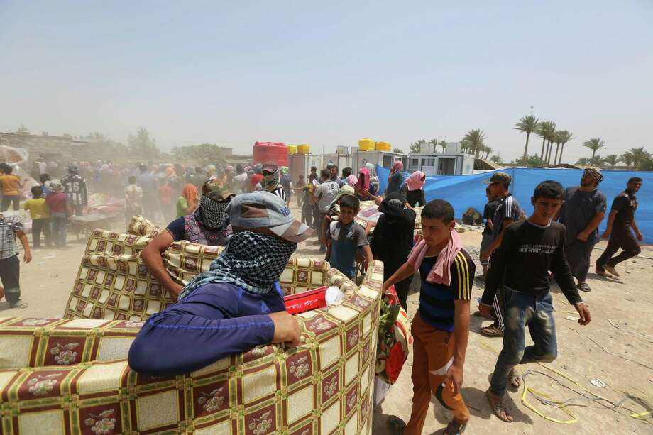 Displaced civilians from Ramadi receive humanitarian aid from the United Nations in a camp in the town of Amiriyat al-Fallujah, west of Baghdad, Iraq, Friday, May 22, 2015. The United Nations World Food Program said it is rushing food assistance into Anbar to help tens of thousands of residents who have fled Ramadi after it was taken by Islamic State militant group. (AP Photo/Hadi Mizban) Photo: Hadi Mizban, STF / Associated Press / AP