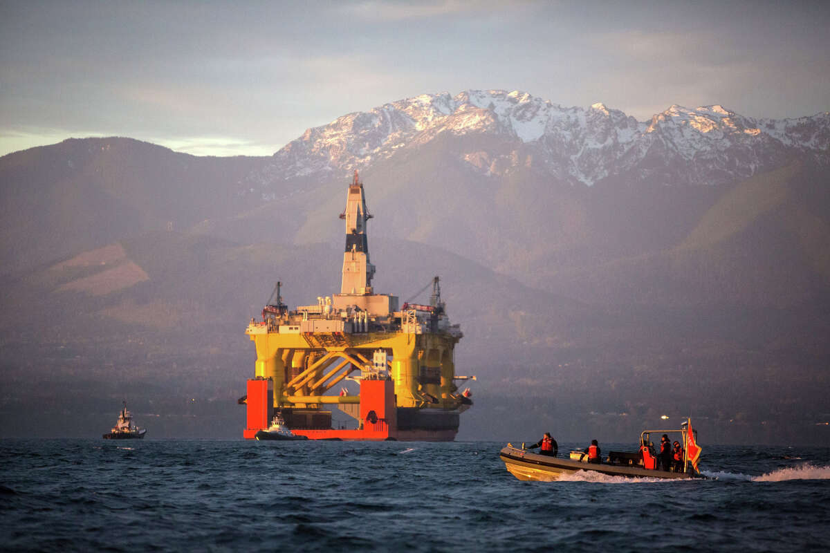 FILE - In this April 17, 2015, file photo, with the Olympic Mountains in the background, a small boat crosses in front of an oil drilling rig as it arrives in Port Angeles, Wash., aboard a transport ship after traveling across the Pacific. Royal Dutch Shell hopes to use the rig for exploratory drilling during the summer open-water season in the Chukchi Sea off Alaska's northwest coast, if it can get the permits. (Daniella Beccaria/seattlepi.com via AP, File) MAGS OUT; NO SALES; SEATTLE TIMES OUT; TV OUT; MANDATORY CREDIT ORG XMIT: WASEA202
