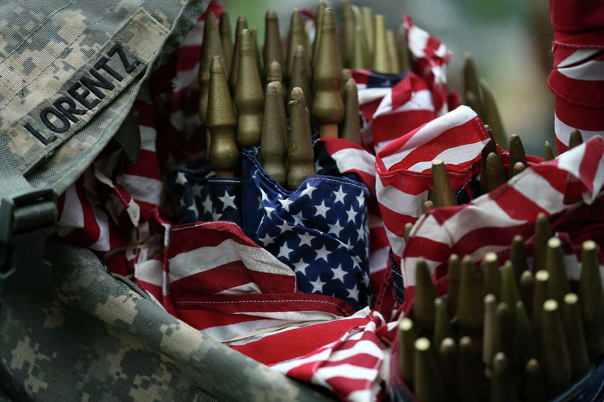 """ARLINGTON, VA - MAY 21: Members of the 3rd U.S. Infantry Regiment load American flags into their backpacks before placing them at the graves of U.S. soldiers buried at Arlington National Cemetery, in preparation for Memorial Day May 21, 2015 in Arlington, Virginia. """"Flags-In"""" has become an annual ceremony since the 3rd U.S. Infantry Regiment (The Old Guard) was designated to be an Army's official ceremonial unit in 1948 (Photo by Win McNamee/Getty Images)"""