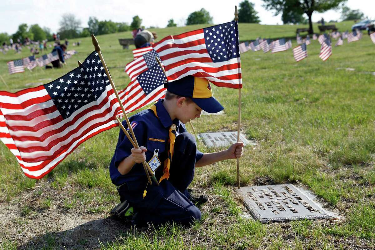 Cub Scout Easton Kulm, 8, of Florence, N.J., places a flag as scouts placed thousands of flags on veteran's graves at Brig. Gen. William C. Doyle Veterans Memorial Cemetery in honor of Memorial Day Friday, May 22, 2015, in Wrightstown, N.J. (AP Photo/Mel Evans)