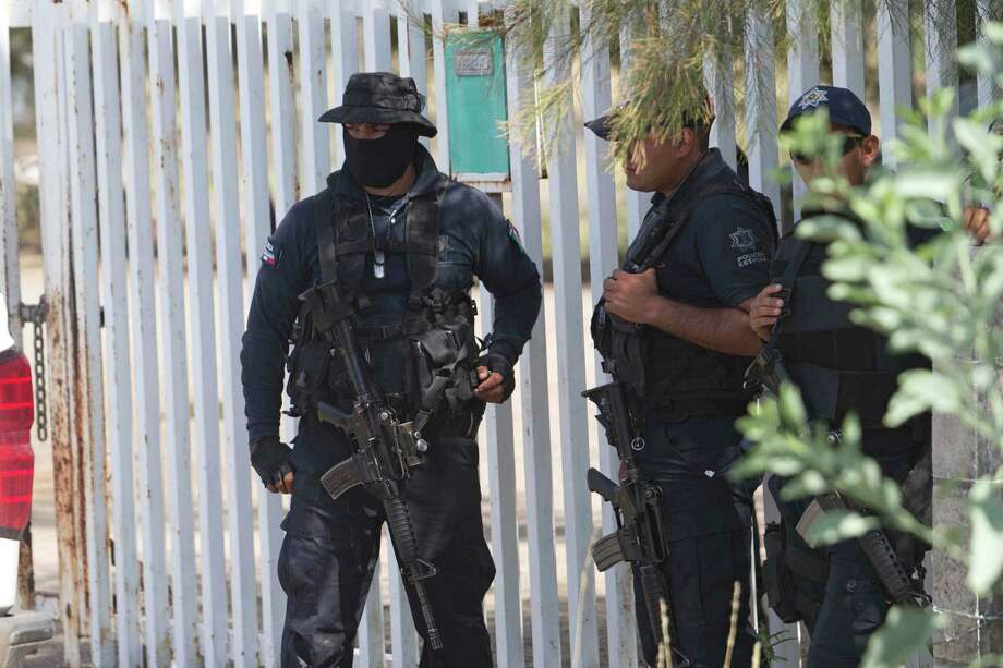 Mexican state police stand guard near the entrance of Rancho del Sol, near Vista Hermosa, Mexico, Friday, May 22, 2015. About 40 people were killed Friday in what authorities described as a large-scale shootout between law enforcement and criminal suspects. Almost all the dead were suspected criminals, said a Federal Police official. The confrontation, which occurred near the border of Michoacan and Jalisco states, started when federal police officers tried to pull over a truck on the highway near the ranch. (AP Photo/Refugio Ruiz) Photo: Refugio Ruiz, STR / AP