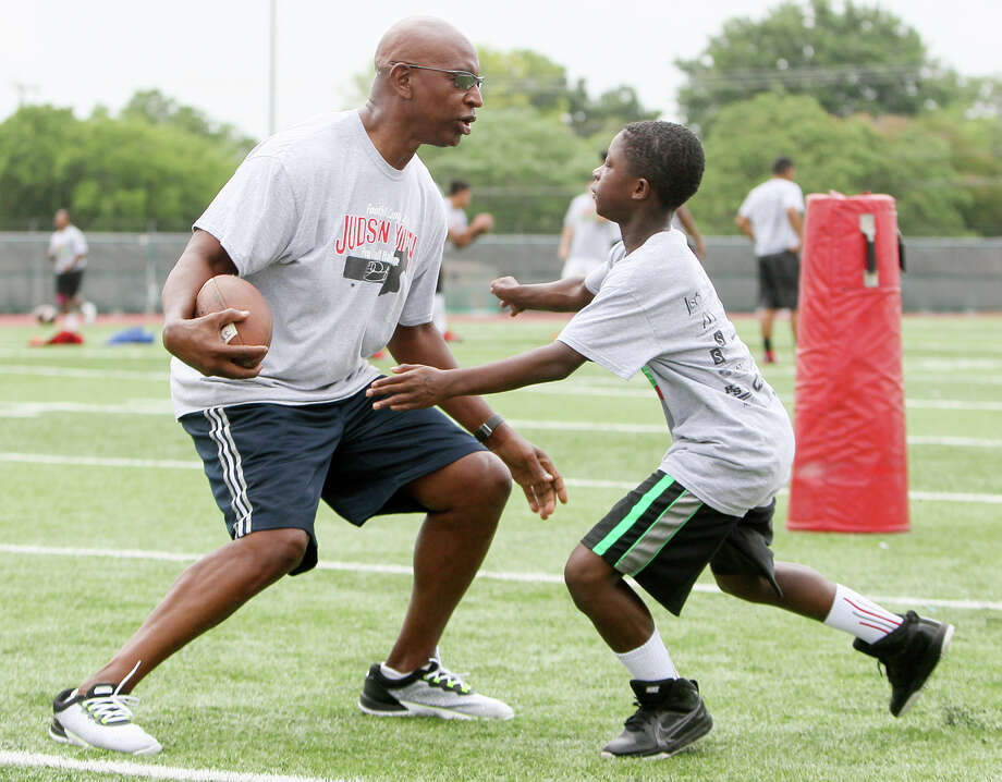 Justin Jones, 12, (right) tries to wrap up Halll of Fame football player Eric Dickerson during the second day of the Judson Education Foundation Footall Camp hosted by Dickerson at Rutledge Stadium on Sunday, June 8, 2014.  The camp had sessions on the basics of football for boys and girls from second grade through high school.  MARVIN PFEIFFER/ mpfeiffer@express-news.net Photo: MARVIN PFEIFFER, STAFF / Marvin Pfeiffer/ Express-News / Express-News 2014