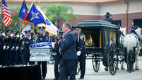 HPD officers salute Richard Martin at his memorial service Friday at Grace Community Church.