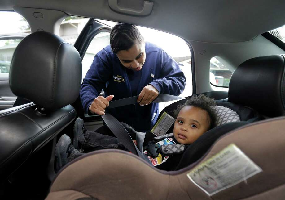 Shannon Henderson buckles her son, Justin, 1, into his car seat before she goes to her job at Wal-Mart in Sacramento, Calif. If she calls in sick, she doesn't get paid. Photo: Rich Pedroncelli, STF / AP