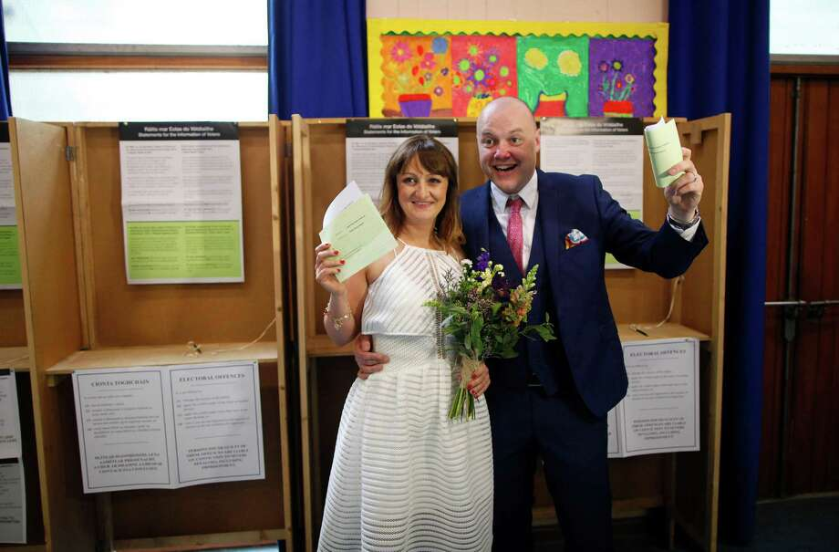 """Newly weds Ann Cole and Vincent Fox prepare to cast their vote at a polling station in Dublin, Ireland, Friday, May 22, 2015.  Ireland began voting Friday in a referendum on Gay marriage which will require an amendment to the Irish constitution. For months, Ireland has debated whether to legalize gay marriage. Now it's time to vote, and the choice is a simple yes or no. Friday's referendum on amending the Irish constitution to give marriage rights to homosexuals is expected to be approved, based on opinion polls that consistently gave """"yes"""" voters a double-digit lead throughout the two-month campaign.  (AP Photo/Peter Morrison) Photo: Peter Morrison, STR / AP"""