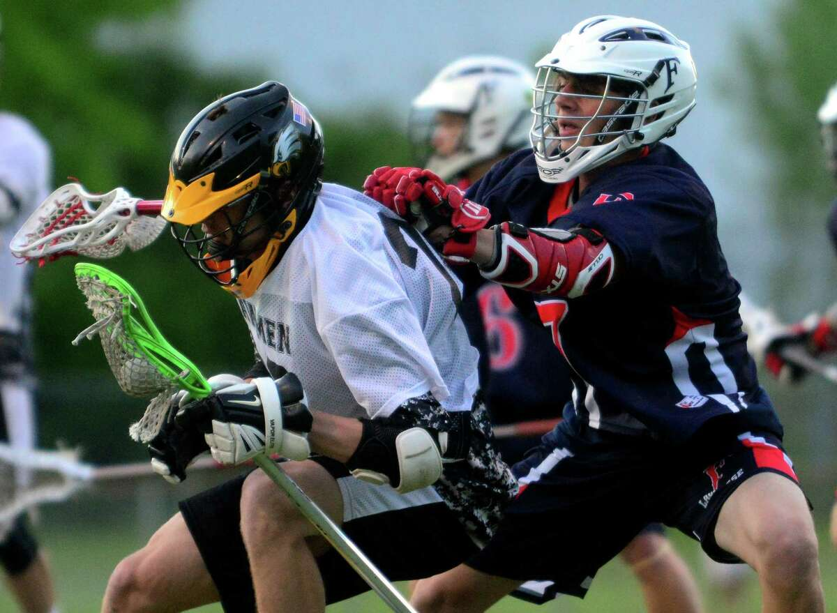 Jonathan Law's Brady Dennigan, left, gets a shove by Foran's Matthew Carrano, during boys lacrosse action in Milford, Conn. on Friday May 22, 2015.