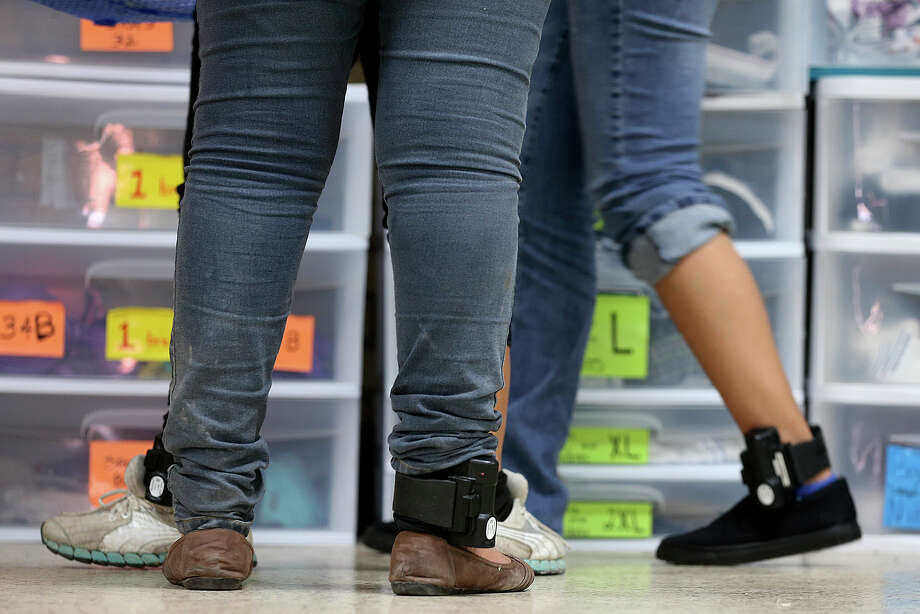 Central American immigrant women wear ankle monitors while getting clothing at the Sacred Heart Catholic Church shelter, Thursday, May 21, 2015. According to volunteers, they started noticing adult immigrants with the monitors, provided by U.S. Customs and Immigration Enforcement, on May 13. After they are processed by immigration, some of the immigrants are released on their own recognizance with a date to appear before an immigration judge at the arrival destination in the US. The monitors are used to insure that they show up before a judge according to an immigration statement. Photo: JERRY LARA, Staff / San Antonio Express-News / © 2015 San Antonio Express-News