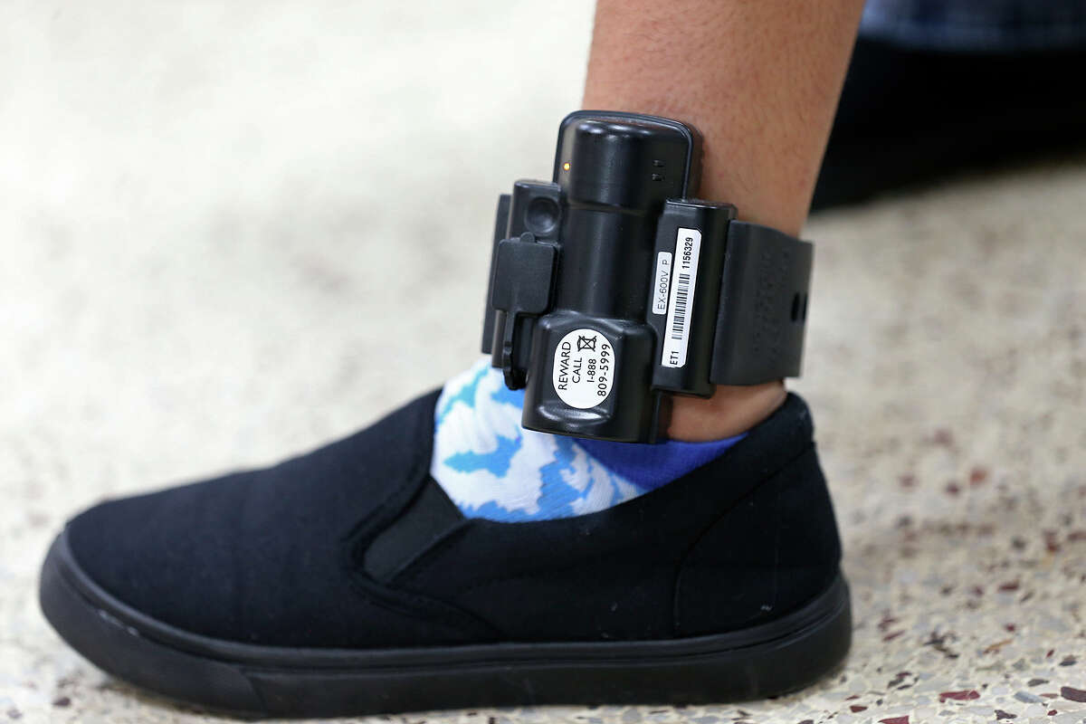 A Central American immigrant shows her ankle monitor while at the Sacred Heart Catholic Church shelter, Thursday, May 21, 2015. According to volunteers, they started noticing adult immigrants with the monitors, provided by U.S. Customs and Immigration Enforcement, on May 13. After they are processed by immigration, some of the immigrants are released on their own recognizance with a date to appear before an immigration judge at the arrival destination in the US. The monitors are used to insure that they show up before a judge according to an immigration statement.