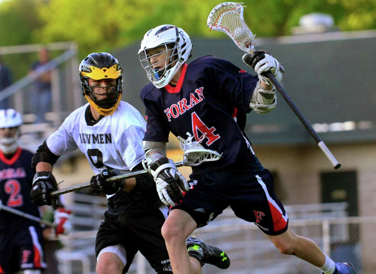 Foran's Jacob Lambert takes the ball behind the goal as Jonathan Law's Jarrod Butts defends, during boys lacrosse action in Milford, Conn. on Friday May 22, 2015.