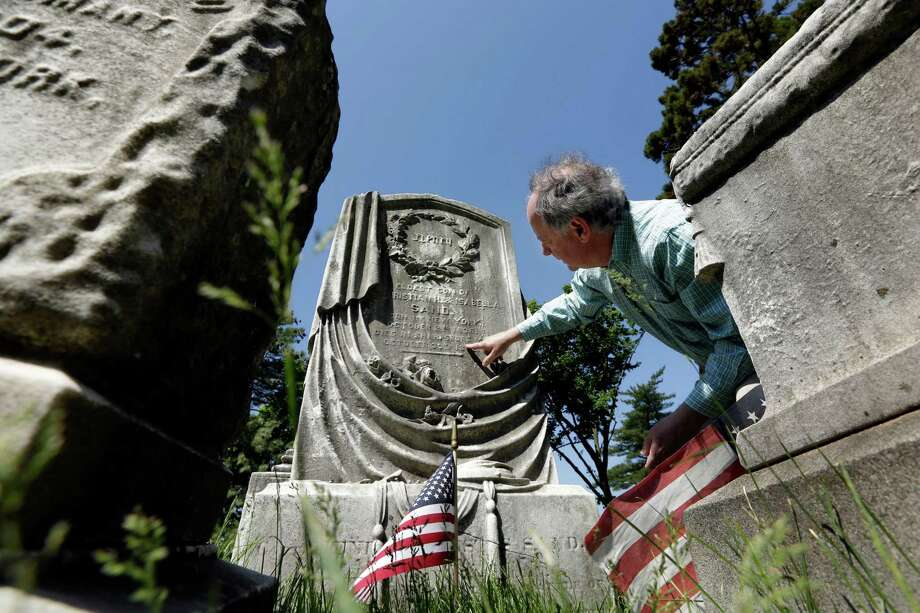 "Resident historian of Green-Wood Cemetery Jeff Richman looks at the grave stone of Capt. Henry Sand of the 103rd New York Volunteer Infantry, in the cemetery in the Brooklyn borough of New York, Friday, May 22, 2015. The cemetery, last resting place for thousands of Civil War veterans, is opening an exhibit, titled ""To Bid You All Good Bye: Civil War Stories,"" commemorating the 150th anniversary of the end of the nation's bloodiest conflict. The title of the exhibit comes from a letter written by Capt. Sand. (AP Photo/Richard Drew) ORG XMIT: NYRD101 Photo: Richard Drew / AP"