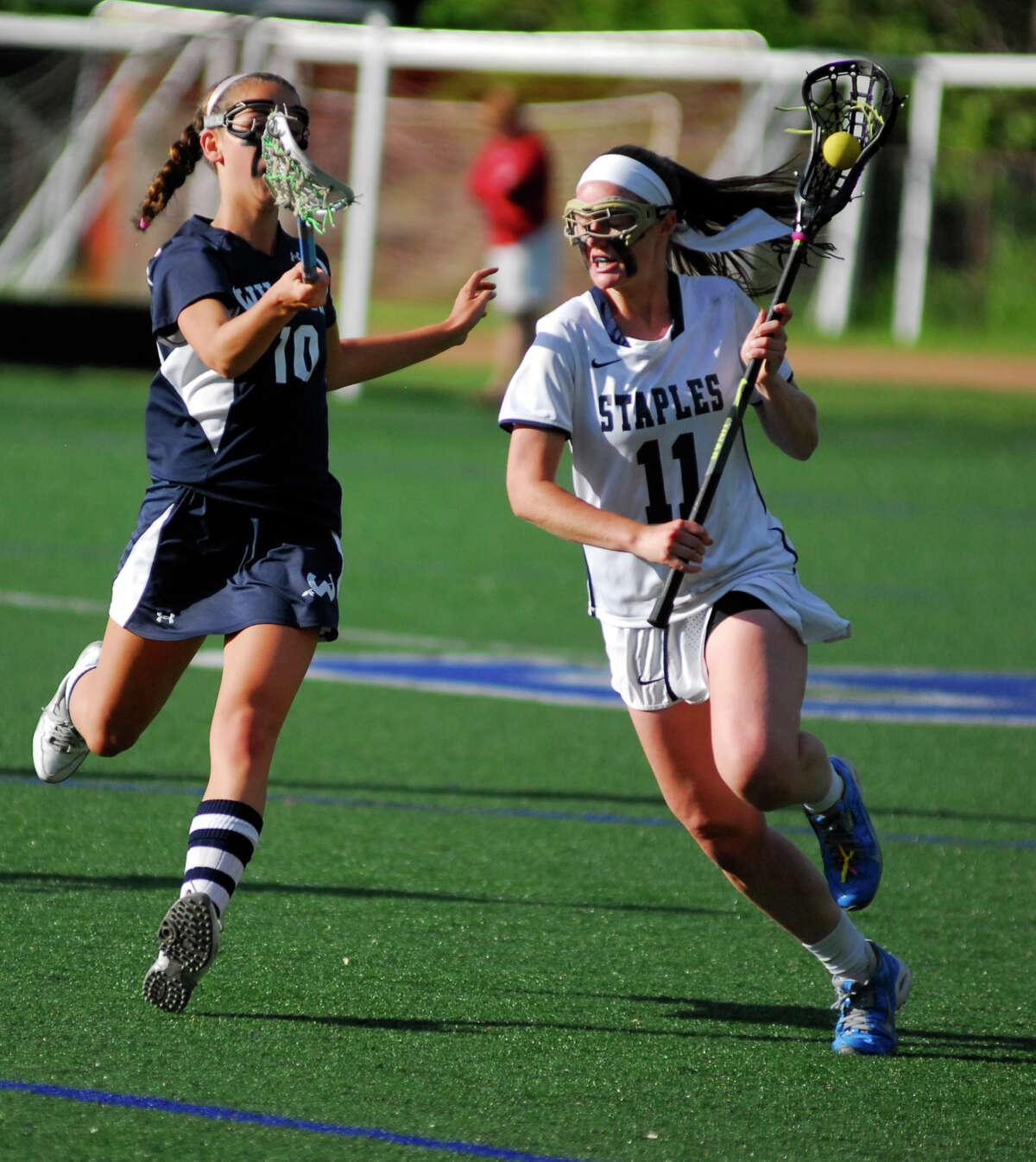 Staples' Colleen Bannon, right, dodges Wilton's Lilla Seymour during a game on Friday. Staples fell 12-10 to the Warriors in the FCIAC quarterfinals.