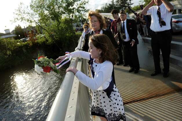 Poppy Queen Julia Boularis, 10, center, tosses a bouquet into the Hudson River in honor of those who served in wars, especially the Navy,  during the Annual American Legion Post 490's Memorial Day Parade on Friday, May 22, 2015, in Stillwater, N.Y. (Cindy Schultz / Times Union) Photo: Cindy Schultz / 00031937A