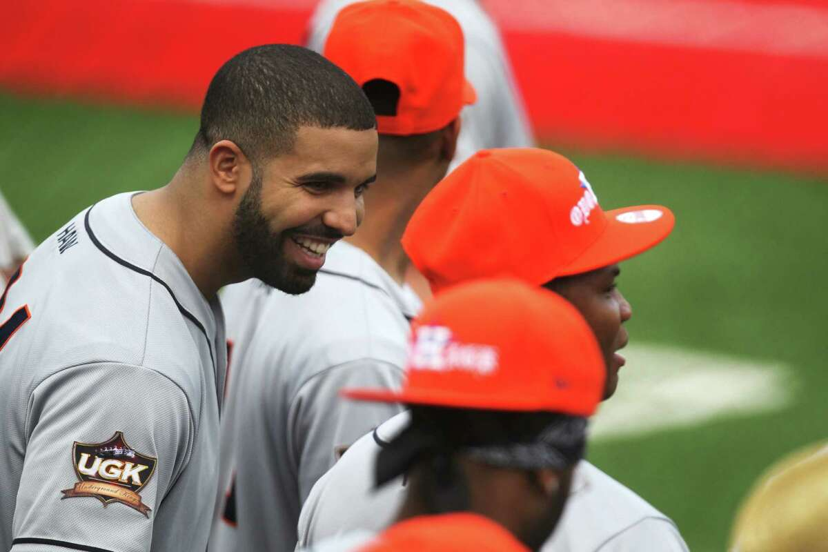 Rap star Drake, left, talks to his teammates during the Drake Celebrity Softball Game on May 22 in Houston.