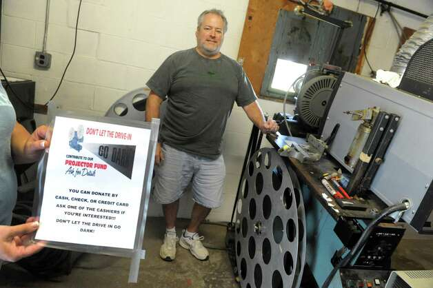 Mike Chenette, center, co-owner of the Jericho Drive-In with his wife Lisa Chenette in their film projection room on Friday, May 22, 2015, in Glenmont, N.Y. The drive-in, which opened for the season Friday night, is in the process of converting from 35mm film stock to digital projection. (Michael P. Farrell/Times Union) Photo: Michael P. Farrell / 00031975A