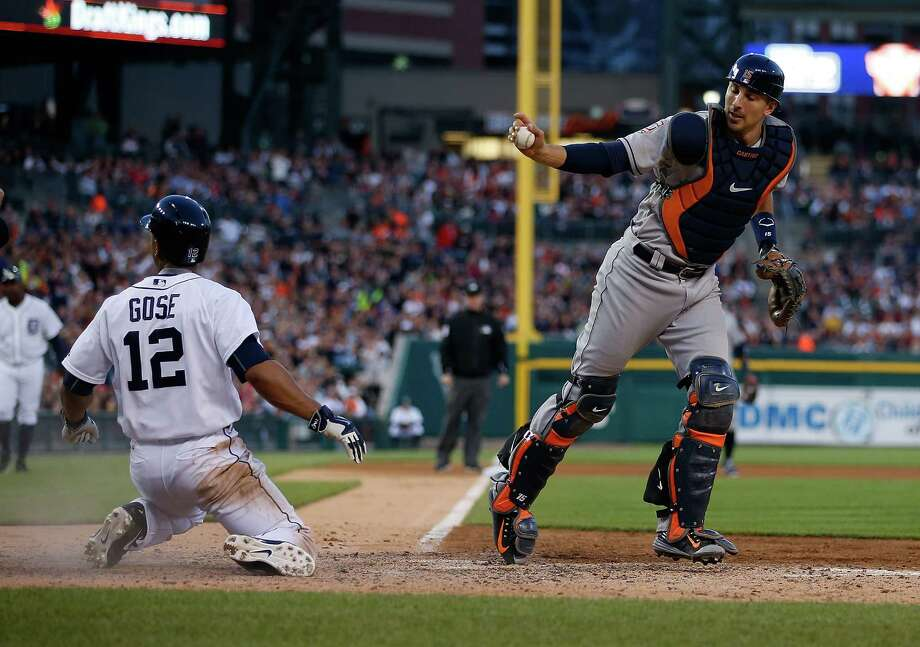 Astros catcher Jason Castro, right, displays the ball as proof after successfully tagging out the Tigers' Anthony Gose, who tried to steal home during the fifth inning of Friday night's game in Detroit. Photo: Gregory Shamus, Stringer / 2015 Getty Images