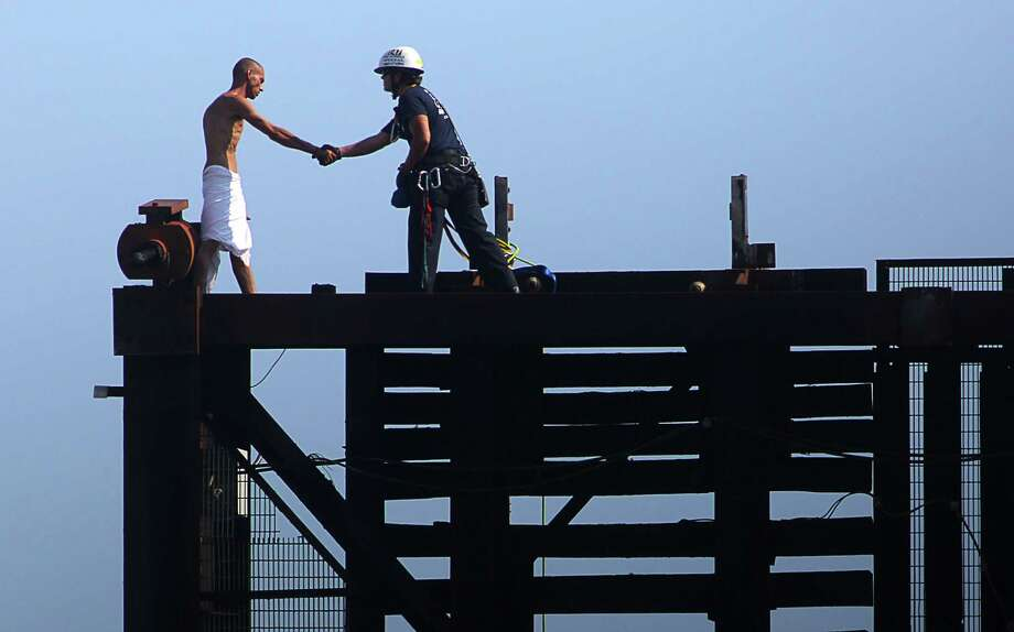 A member of the Broward Sheriff's Office rescues a naked man on top of a raised drawbridge on Friday, May 22, 2015 in Fort Lauderdale, Fla.   Witnesses said the unidentified man was swimming in the river earlier and was walking across the railroad bridge Friday morning when it began to rise, forcing him to scamper to the top.   (Michael Clary/South Florida Sun-Sentinel via AP)  MAGS OUT Photo: Michael Clary, MBO / South Florida Sun-Sentinel