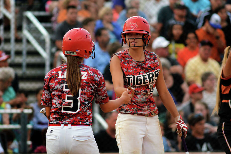 Katy's Kat Lopez, left, is congratulated by teammate  Nicole Valdez after Lopez scored one of the Tigers' three runs in the fifth inning Friday night. Photo: Jerry Baker, Freelance