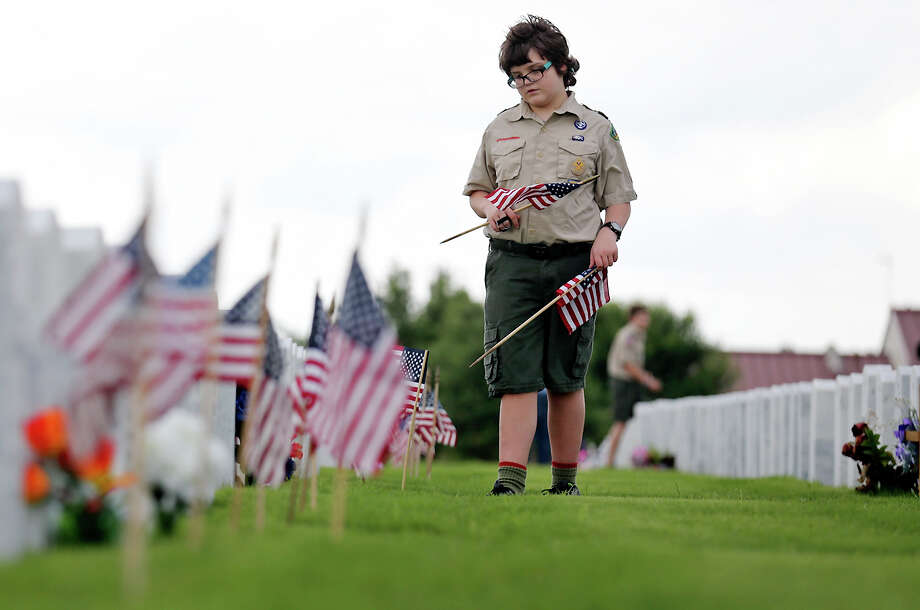 Boy Scout Joseph Vlach, 13, of Troop 90, places American flags on graves Friday at Fort Sam Houston National Cemetery. Photo: Edward A. Ornelas /San Antonio Express-News / © 2015 San Antonio Express-News