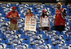 Houston Rockets fans watch the Houston Rockets and Rockets warm up as one of them holds a sign that reads, Clutch City, before Game 4 of an NBA basketball first-round playoff series against the Dallas Mavericks, Sunday, April 26, 2015, in Dallas. (AP Photo/Tony Gutierrez)