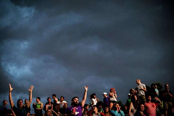 Despite storm clouds overhead, fans rock out to the sounds of the main stage on the first of four days of the annual Sasquatch music festival Friday, May 22, 2015, at The Gorge Amphitheatre in George, Washington.