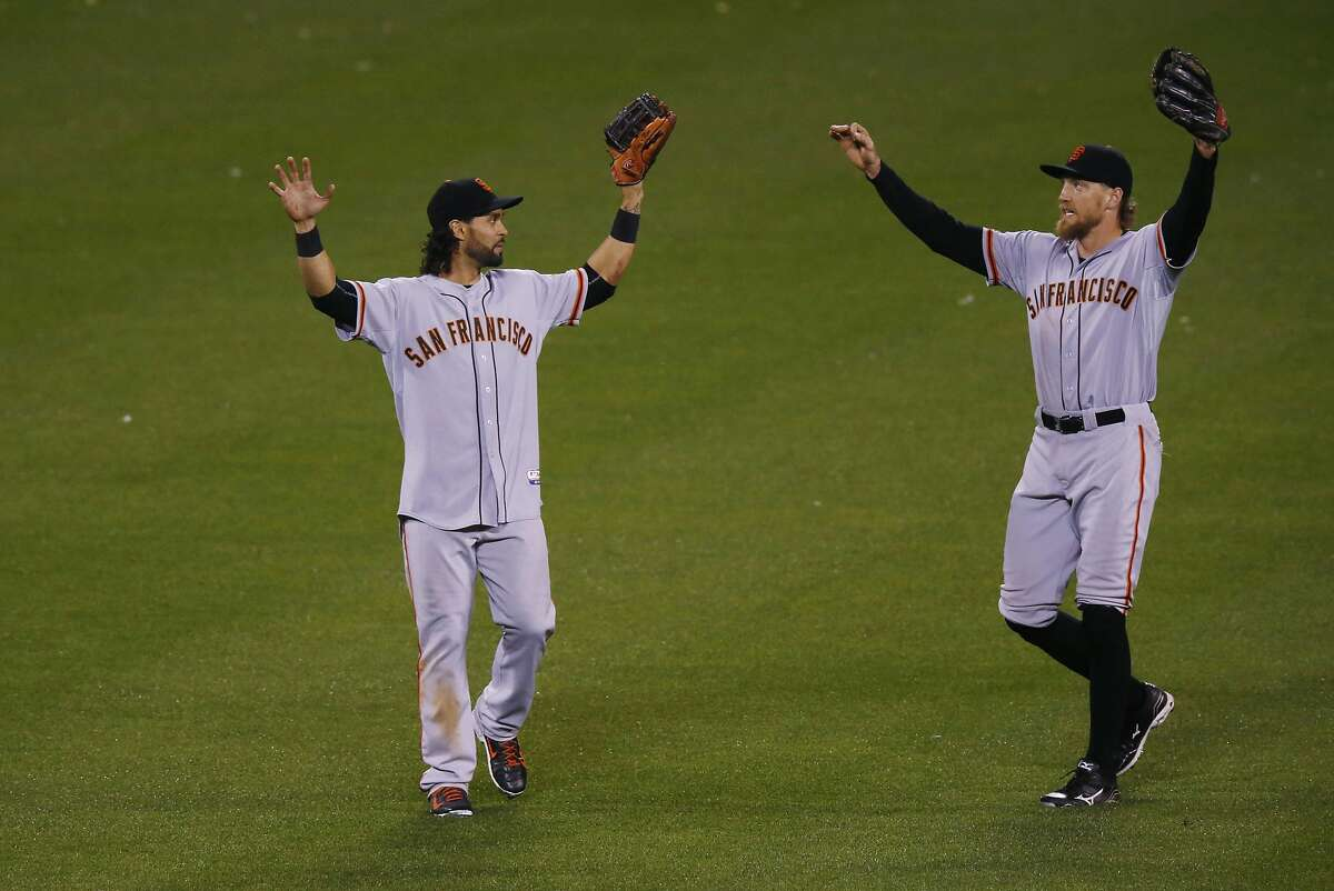 San Francisco Giants center fielder Angel Pagan, left, celebrates with San Francisco Giants right fielder Hunter Pence after the Giants retired the Colorado Rockies in the bottom of the ninth inning of a baseball game Friday, May 22, 2015, in Denver. The Giants won 11-8. (AP Photo/David Zalubowski)