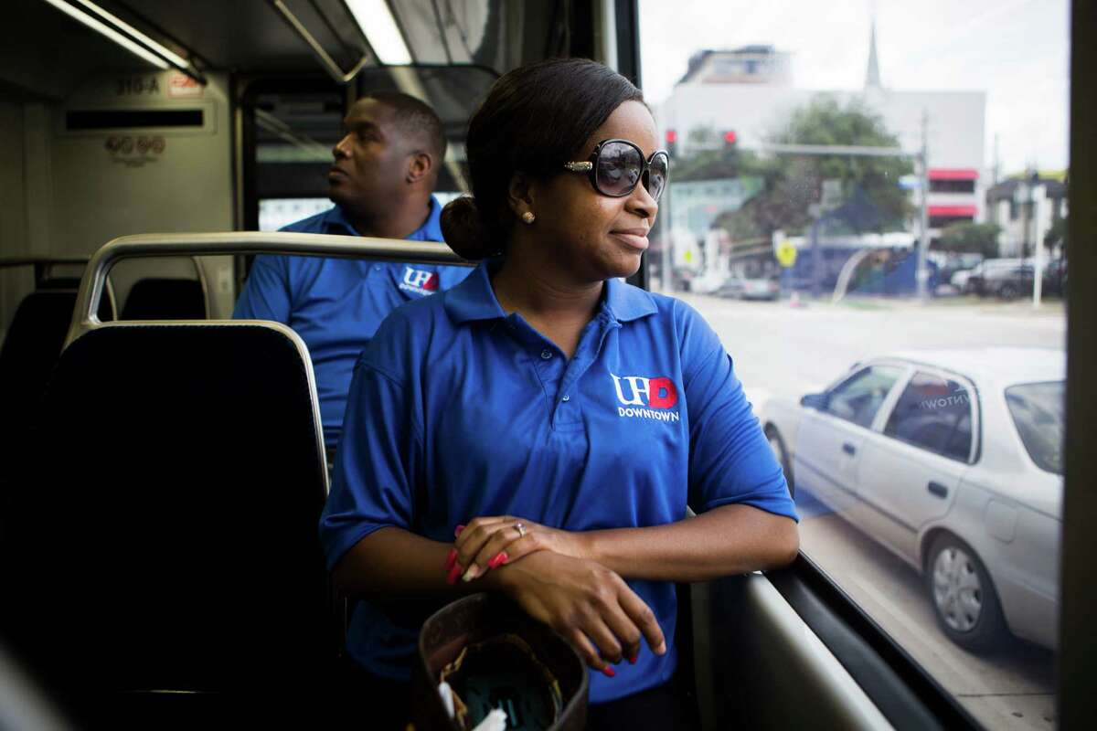 Sherrigo McNeil, foreground, and Brian Blackwell take a ride toward downtown Houston on the new Green Line Metro to pick up their cars after going to the The University of Houston Downtown Spring 2015 Commencement exercises at Minute Maid Park on May 23.