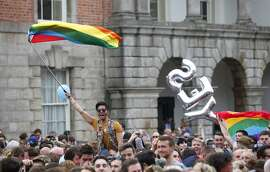 """Yes supporters celebrate at Dublin castle, Ireland, Saturday, May 23, 2015. Ireland has voted resoundingly to legalize gay marriage in the world's first national vote on the issue, leaders on both sides of the Irish referendum declared Saturday even as official ballot counting continued. Senior figures from the """"no"""" campaign, who sought to prevent Ireland's constitution from being amended to permit same-sex marriages, say the only question is how large the """"yes"""" side's margin of victory will be from Friday's vote. (AP Photo/Peter Morrison)"""