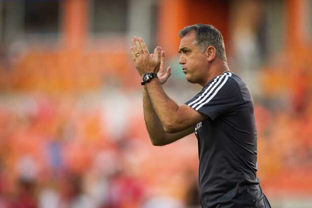 Houston Dynamo head coach Owen Coyle enters the field minutes before the game between the Houston Dynamo and the Portland Timber, Saturday, May 16, 2015, in Houston.
