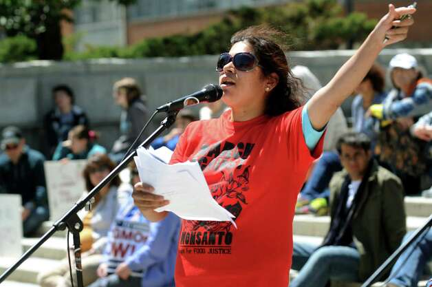 Volunteer and organizer Dally Sanchez, center, reads a list of politicians in Washington D.C. who support Monsanto during the March Against Monsanto on Saturday, May 23, 2015, at the Capitol in Albany, N.Y. The event was part of an international day of protest against Monsanto's corporate farming and business practices and to support labeling of foods that contain genetically engineered and modified materials. (Cindy Schultz / Times Union) Photo: Cindy Schultz / 00031934A