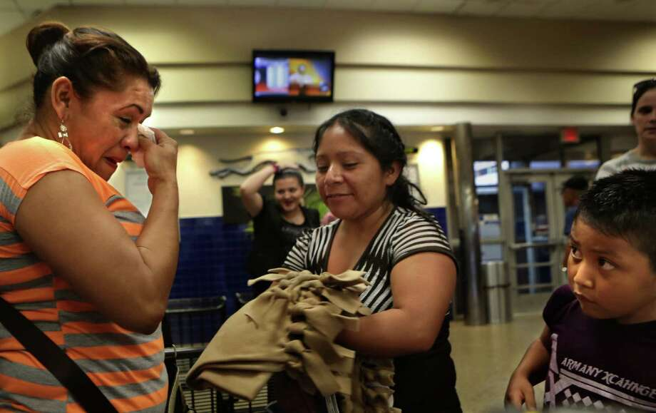 Yanira Lopez, left, wipes away tears after running into a friend from the Karnes County Detention Center at the San Antonio Greyhound bus station unexpectedly.  The Interfaith Welcome Coalition will typically pick up immigrants from the detention center and offer them shelter until they can travel to live with family or their immigration cases are heard.  The Coalition will also greet immigrants at the bus station to help facilitate travel and offer any needed services. Photo: Bob Owen, Staff / San Antonio Express-News / San Antonio Express-News