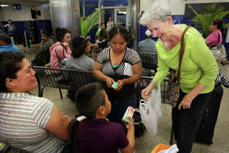 Janice Clayton of Laurel Heights Methodist Church in San Antonio provides drinks to a Guatemalan family on their way from San Antonio to Los Angeles where they have family member. Clayton is part of the Interfeaithy welcome Coalition which helps facilitate immigrant transitions and travel after being released from detention centers. Photo: Bob Owen / San Antonio Express-News / San Antonio Express-News