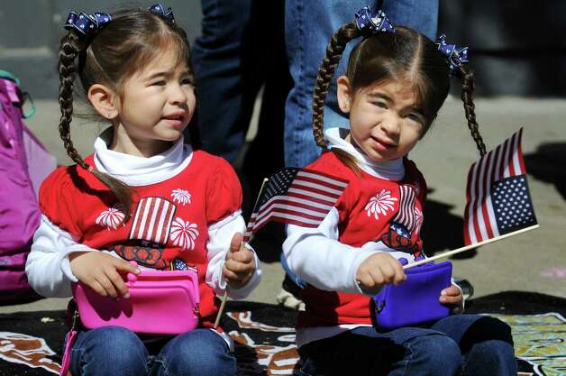 Anabelle Perez, 3, left, and her twin sister Ava Perez, 3, of Ballston Spa wave flags during the Ballston Spa Memorial Day Parade on Saturday, May 23, 2015, in Ballston Spa, N.Y. (Cindy Schultz / Times Union) Photo: Cindy Schultz / 00031958A