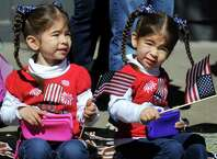 Anabelle Perez, 3, left, and her twin sister Ava Perez, 3, of Ballston Spa wave flags during the Ballston Spa Memorial Day Parade on Saturday, May 23, 2015, in Ballston Spa, N.Y. (Cindy Schultz / Times Union)
