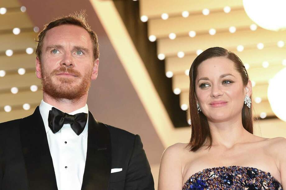 "German-Irish actor Michael Fassbender (L) and French actress Marion Cotillard pose before leaving the Festival palace after the screening of the film ""Macbeth"" at the 68th Cannes Film Festival in Cannes, southeastern France, on May 23, 2015.   AFP PHOTO / ANNE-CHRISTINE POUJOULATANNE-CHRISTINE POUJOULAT/AFP/Getty Images Photo: ANNE-CHRISTINE POUJOULAT, Staff / AFP / Getty Images / AFP"