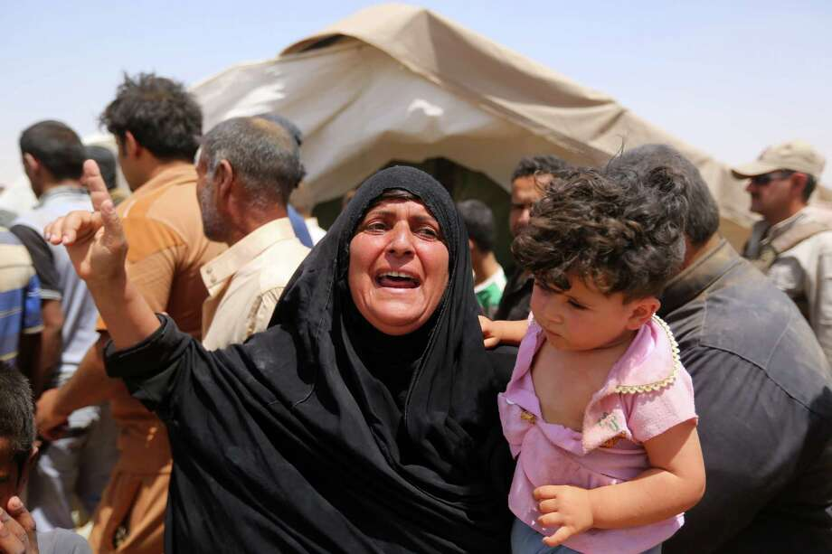 A women who fled Ramadi holds a child  in a camp in the town of Amiriyat al-Fallujah, west of Baghdad, Iraq, Friday, May 22, 2015. The United Nations World Food Program said it is rushing food assistance into Anbar to help tens of thousands of residents who have fled  Ramadi after it was taken by Islamic State militant group. (AP Photo/Hadi Mizban) ORG XMIT: ZHM112 Photo: Hadi Mizban / AP