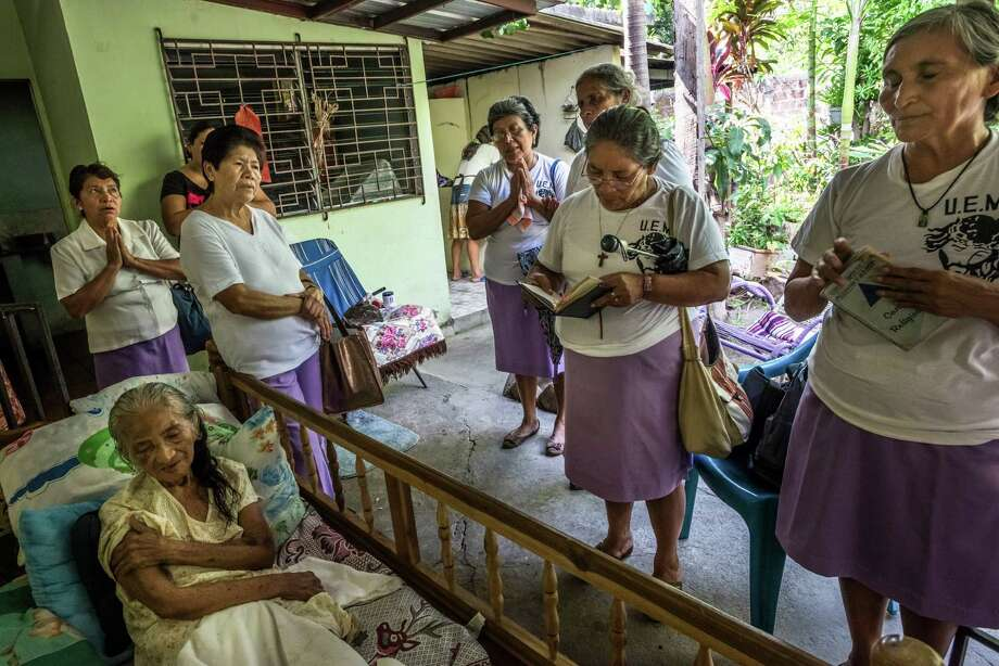 Missionaries pray for Carmen Ayala Lopez, 80, in San Salvador, El Salvador, May 22, 2015. The women are followers of Salvadoran Archbishop Oscar Romero, who was murdered in 1980 and beatified in a ceremony Saturday in San Salvador, leaving him one step from sainthood. (Meridith Kohut/The New York Times) ORG XMIT: XNYT38 Photo: MERIDITH KOHUT / NYTNS
