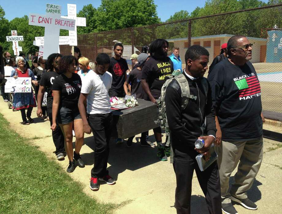 Protestors walk in a mock funeral procession in a park after the verdict of officer Michael Brelo, on Saturday, May 23, 2015, in Cleveland. Brelo, a police officer charged in the shooting deaths of two unarmed suspects, Timothy Russell and Malissa Williams, was acquitted, Saturday. (AP Photo/Andrew Welsh-Huggins) ORG XMIT: RPAW102 Photo: Andrew Welsh-Huggins / ap
