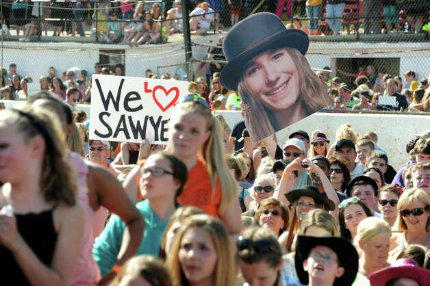 Fans listen and hold signs as FultonvilleOs own Sawyer Fredericks performs at the Fonda Speedway on Wednesday, May 6, 2015 in Fonda, N.Y. The 16-year-old singer/songwriter is one of the final six contestants on NBCOs show The Voice. (Lori Van Buren / Times Union) Photo: Lori Van Buren / 00031668A