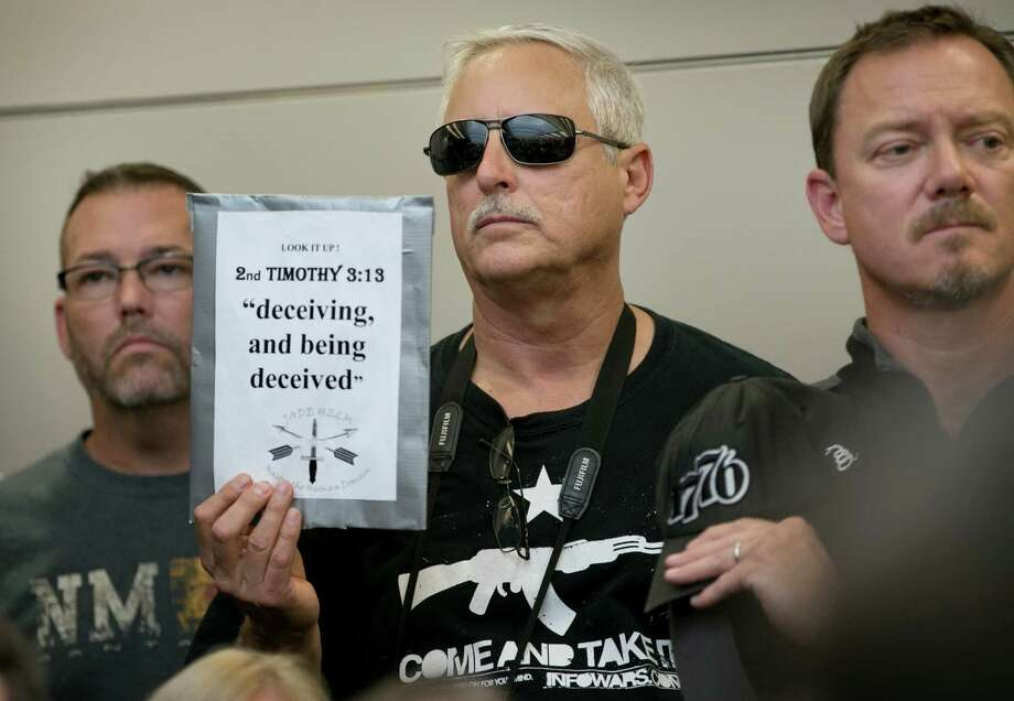 Bob Welch holds a warning sign during a public hearing in Bastrop about the Jade Helm 15 military training exercise. Photo: Jay Janner / Austin American-Statesman / Austin American-Statesman