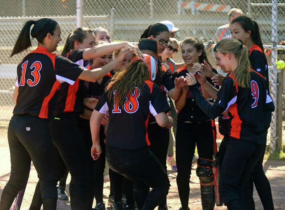 Stamford's Lauren O'Neill is surrounded by teammate after hitting a home run, during softball action against Norwalk in Stamford, Conn., on Saturday May 23, 2015. Photo: Christian Abraham / Connecticut Post