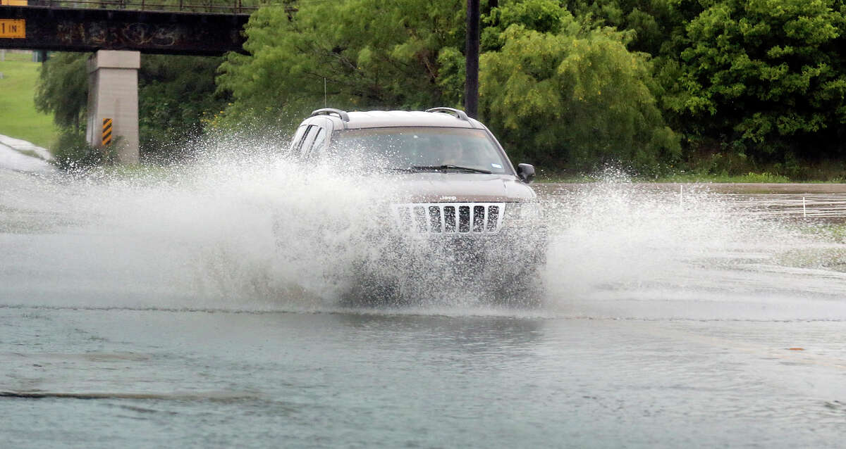 Motorists drive through high water at the intersection of N. New Braunfels Ave. and Retama Pl. Saturday May 23, 2015 as storms move through the area.