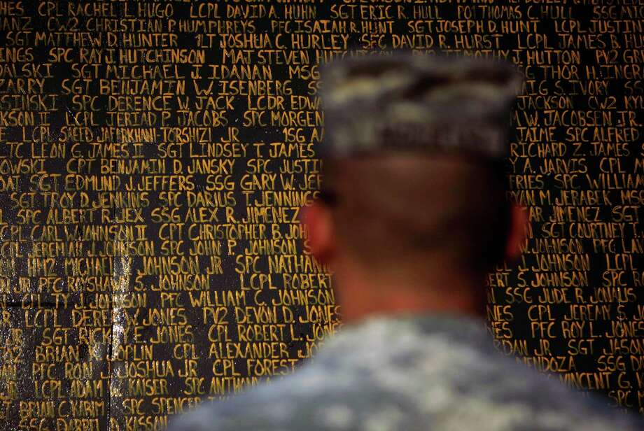 In 2010, then-Sgt. Kevin McCulley stands in front of one panel in a monument bearing the names of more than 4,300 U.S. service members killed in Iraq. Photo: Maya Alleruzzo, STF / AP