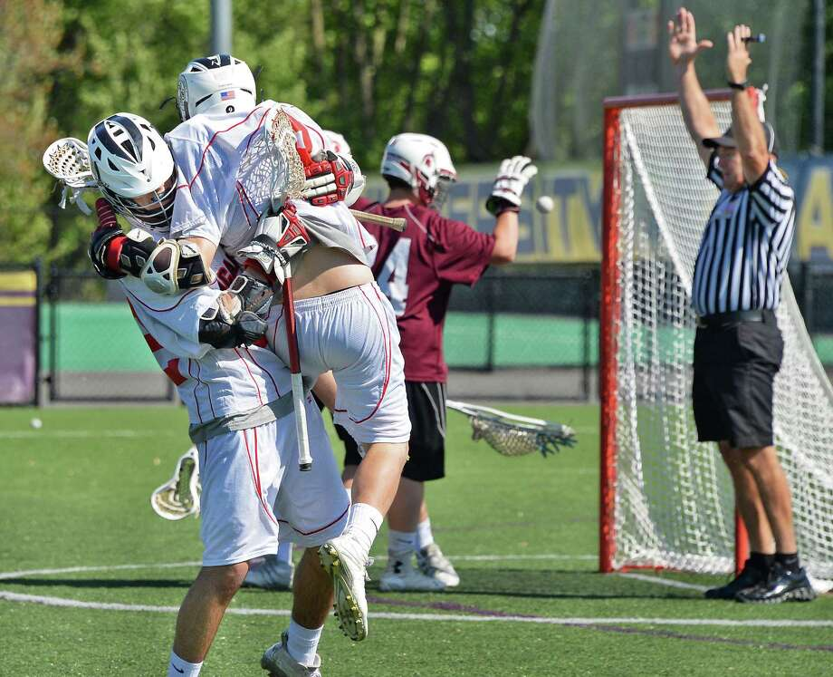 Albany Academy's #22 Andrew Martin, left, hugs team mate #9 Brevin Fleischer after Brevin's goal against Burnt Hills's goalie #24 Dan Biesty during the Section II Class B boys' lacrosse final at John Fallon Field Saturday May 23, 2015, in Albany, NY. (John Carl D'Annibale / Times Union) Photo: John Carl D'Annibale / 00031878A