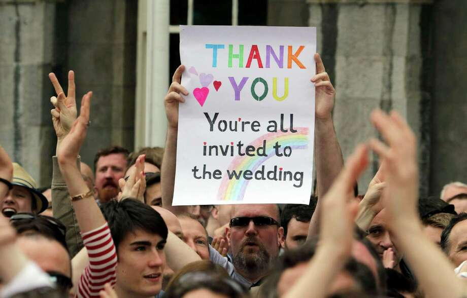 A supporter's sign reads 'Thank You - You're All Invited to the Wedding' as he celebrates outside Dublin Castle after the gay marriage referendum Saturday. Photo: PAUL FAITH, Stringer / AFP