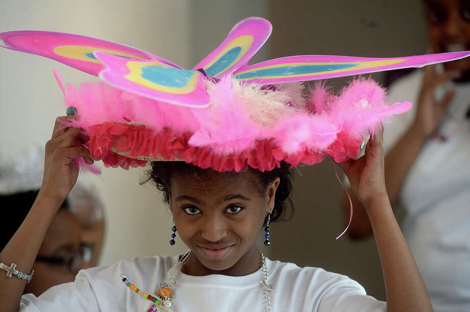 "India Charles, 11, adjusts her colorful, butterfly topped hat as she prepares for the YWCA's Mad Hatter Project fashion show and tea party at the Art Museum of Southeast Texas Saturday. For five weeks, girls have gathered at the Beaumont Art League studio, learning to sew, bedazzle, make jewelry and expand their creativity and self-expression in the second annual hat-making project. Each work session also included ""girl talk"" time with guest speakers who addressed issues relating to girls' self-confidence and empowerment. Saturday's fashion show allowed them to showcase that confidence along with their creative journey, as the girls modeled their work and shared personal stories of growth through the project. The girls used recycled materials to create their pieces, with project funding support by Community Health Choice and Jason's Deli. Photo taken Saturday, May 23, 2015 Kim Brent/The Enterprise Photo: Kim Brent / Beaumont Enterprise"