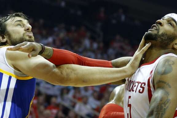 Golden State Warriors center Andrew Bogut (12) and Houston Rockets forward Josh Smith (5) get tangled up under the basket during the first quarter of Game 3 of the NBA Western Conference finals at the Toyota Center on Saturday, May 23, 2015, in Houston.  ( James Nielsen / Houston Chronicle )
